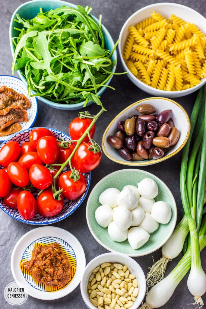 Leichter kalorienarmer Nudelsalat italienischer mit Pesto, Rucola und Mozzarella (vegetarisch und perfekt zum Grillen). Toller Sommersalat ohne Mayonnaise. Lässt sich mit Oliven, getrockneten Tomaten, frischen Tomaten, Rucola, Babyspinat, Mozzarella, Feta und Pinienkernen nach Geschmack abwandeln. Rucola erst kurz vor dem Essen dazugeben, damit er knackig bleibt. Fettarm und gesund. Gesundes und kalorienarmes Kochen. Schnelle und einfache Rezepte zum Abnehmen. - kaloriengeniessen.de #salat #nudelsalat #italienisch #pesto #machtsatt #mittagessen #rucola #mozzarella # fusilli #Grillen #kalorienarm #gesund #kalorienarmerezepte #kaloriengeniessen #rezeptezumabnehmen