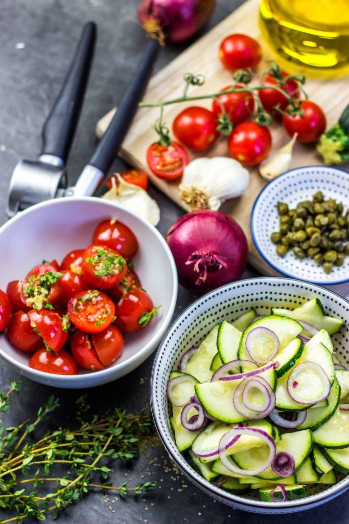 Gesunder Lachs aus dem Ofen mit mediterranem Gemüse aus Zucchini und Tomaten. Herzhaft und perfekt für den Grill oder den Backofen. Super Mittagessen und Abendessen während einer Diät. Kalorienarmes Kochen. Schnelle Rezepte zum Abnehmen. - kaloriengeniessen.de #zucchini #lachs #tomaten #ofen #grill #herzhaft #schnellundeinfach #kaloriengeniessen #rezeptezumabnehmen