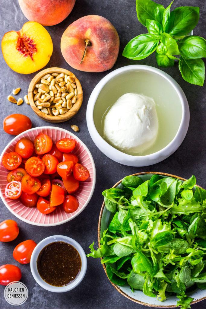 Sommer-Salat mit Pfirsichen, Tomaten, Mozzarella, Pinienkernen und einen leckeren Honig-Balsamico-Dressing. Zum Pfirsich-Salat passt auch Feta oder cremiger Ziegenkäse besonders gut! Als kalorienarmes Mittagessen perfekt für warme Tage. Gesundes und kalorienarmes Kochen. Schnelle und einfache Rezepte zum Abnehmen. - kaloriengeniessen.de #salat #pfirsich #feta #schnellundeinfach #kaloriengeniessen #rezeptezumabnehmen #mozzarella #nektarine #dressing #sommersalat