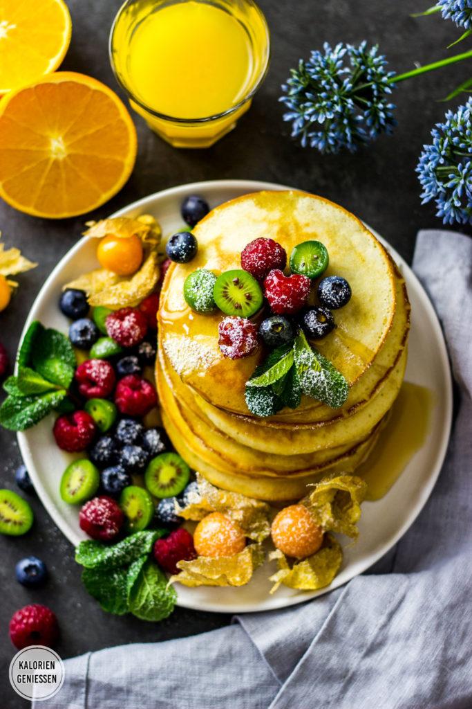 Die fluffigsten und dicksten Pfannkuchen, die ich jemals gemacht habe. Einfaches Rezept mit wenig Zutaten. Fettarm und gesund mit Buttermilch und Früchten. Ein Pfannkuchen hat nur 100 Kalorien. Perfekt zum Frühstück, als Mittagessen oder zum Nachmittagskaffee. Die kalorienarmen Pfannkuchen sind zum Einfrieren sehr gut geeignet: Einfach zwischen die einzelnen Pancakes Butterbrotpapier legen – so lassen sie sich auch einzeln entnehmen. Gesundes und kalorienarmes Kochen. Schnelle und einfache Rezepte zum Abnehmen. - kaloriengeniessen.de #pfannkuchen #pancakes #fluffig #grundrezept #machtsatt #dessert #mittagessen #frühstück #kalorienarm #gesund #kalorienarmerezepte #kaloriengeniessen #rezeptezumabnehmen