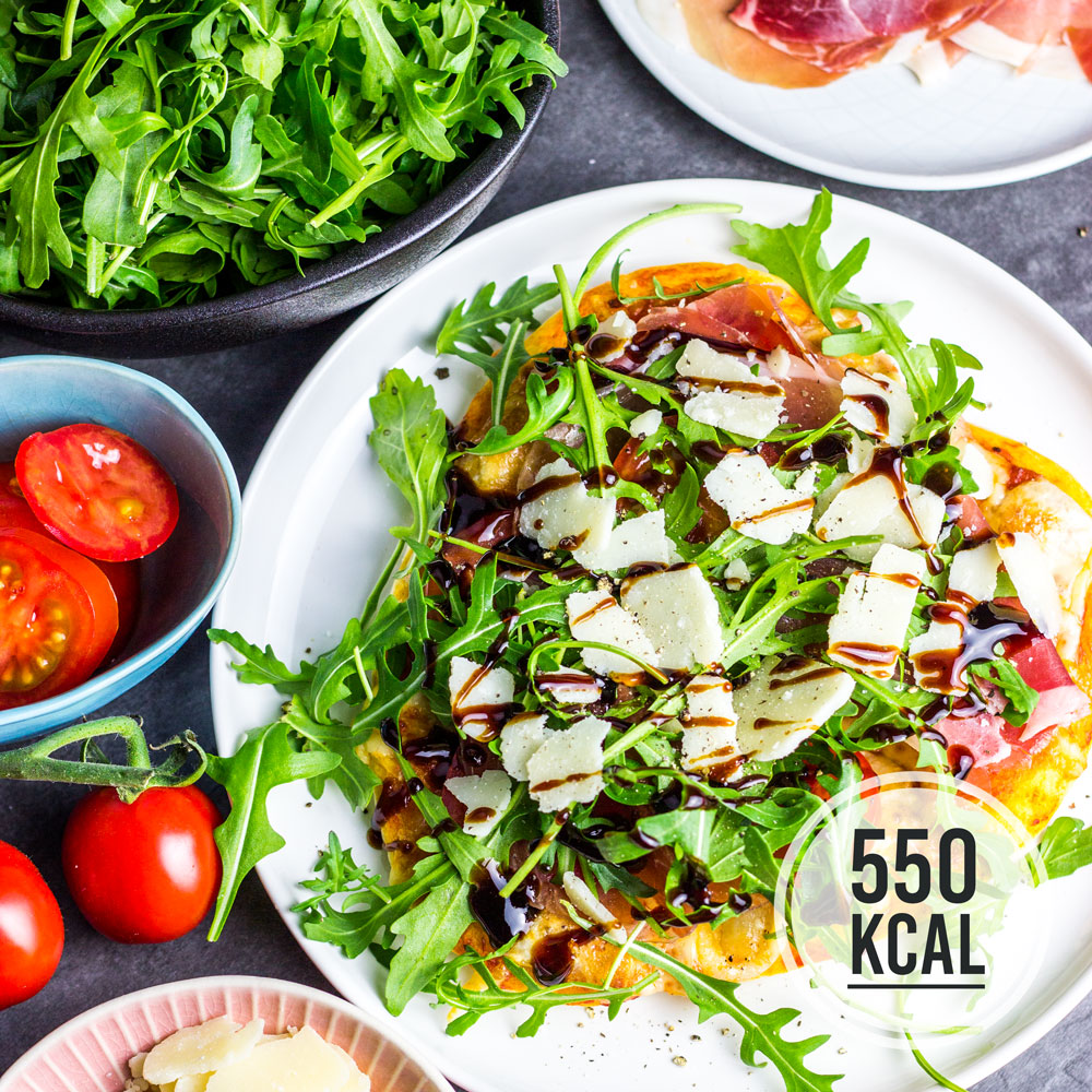 Selbstgemachte und kalorienarme Pizza mit Rucola, Schinken, Tomaten und Parmesan. Mit frischen Teig aus dem Kühlregal. 550 Kalorien für eine Rucola-Parmaschinken-Pizza. Kalorienarmes Essen. Gesundes und kalorienarmes Kochen. Schnelle und einfache Rezepte zum Abnehmen. - kaloriengeniessen.de #pizza #selbstgemacht #schinken #parmaschinken #rucola #parmesan #gesund #italienisch #kalorienarmerezepte #kaloriengeniessen #rezeptezumabnehmen